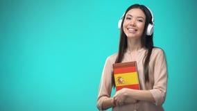 Lições audio espanholas de escuta da menina nos auriculares, livro nas mãos, traduções filme