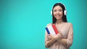 Lições audio francesas de escuta da menina nos auriculares, livro nas mãos, traduções vídeos de arquivo