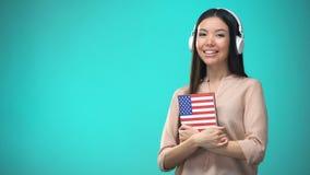 Lições audio inglesas americanas de escuta da estudante nos auriculares, livro nas mãos filme