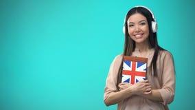 Lições audio inglesas britânicas de escuta da estudante nos auriculares, livro nas mãos vídeos de arquivo
