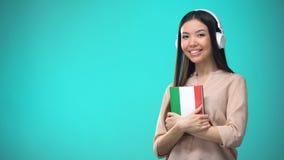 Lições audio italianas de escuta da menina nos auriculares, livro nas mãos, traduções vídeos de arquivo