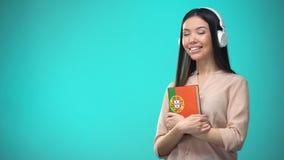 Lições audio portuguesas de escuta da menina nos auriculares, livro nas mãos, traduções filme