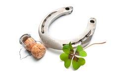 Liège de fer à cheval et de champagne avec un trèfle de quatre feuilles Image stock