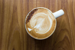 Liść kształtująca kawy mleka piana w białej ceramicznej filiżance fotografia stock