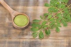 Liście i Moringa proszek Drewniany tło - Moringa oleifera zdjęcia stock