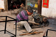Li 'An, China: Man Cutting Pipe Stock Images