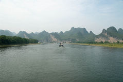 The Li River in China. Tour boats travelling down the Li River with the rounded limestone mountains in the background Royalty Free Stock Image