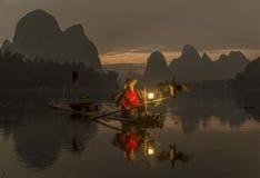 Li River - Xingping, China Em janeiro de 2016 - uma pesca velha do pescador com seus cormorões Imagens de Stock Royalty Free