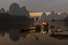 Li River - Xingping, China. January 2016 - An old fisherman gets ready to go out fishing with his cormorants. Stock Photography