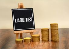 Liabilities black board with golden coins stack Stock Photography