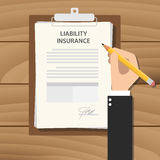 Liability insurance concept illustration with business man hand signing a paper work document on clipboard  wooden table Stock Photo