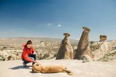 Liaison femelle heureuse de voyageur avec le chien local sur les cheminées féeriques Images stock