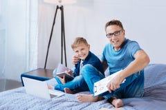 Liaison heureuse de père et de fils tout en faisant le travail ensemble Photos stock