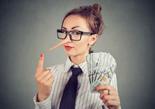 Liar businesswoman with dollar cash and sly look. Financial fraud concept. Liar businesswoman with dollar cash and sly look royalty free stock images