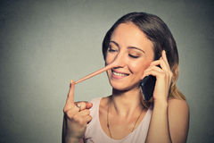 Liar concept. Happy woman with long nose talking on mobile phone Stock Photos