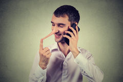 Liar customer service representative. Happy man with long nose talking on mobile phone Stock Photography