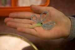 Libélula feita dos grânulos na mão do ` s da criança Foto de Stock Royalty Free
