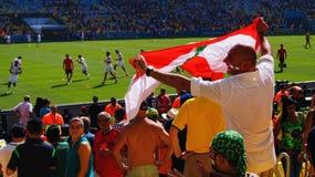 Libanesisches Fußballfan, das der Libanon-Flagge wellenartig bewegt lizenzfreie stockbilder