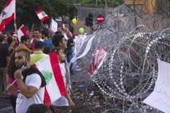 Libanesiska protester Folk med flaggor av Libanon på en protestmarsch Den fridsamma protesten eskalerade arkivfoto