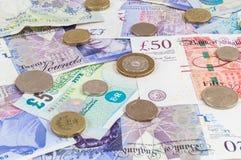 Libbre britanniche di banconote e fondo delle monete Fotografia Stock