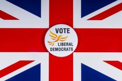 Liberal Democrats Political Party in the UK. London, UK - November 20th 2018: A Liberal Democrats political party badge, pictured over the flag of the United royalty free stock photography