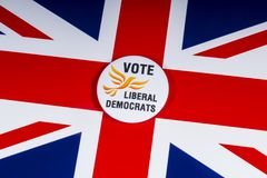 Liberal Democrats Political Party in the UK. London, UK - November 20th 2018: A Liberal Democrats political party badge, pictured over the flag of the United royalty free stock images