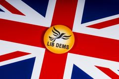 Liberal Democrats Political Party in the UK. London, UK - November 20th 2018: A Liberal Democrats political party badge, pictured over the flag of the United royalty free stock photos
