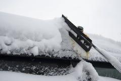 Liberando il tetto dell'automobile dalla spazzola della neve Fotografie Stock