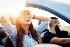 Liberdade da estrada aberta Pares novos que conduzem ao longo da estrada secundária no carro superior aberto fotografia de stock royalty free