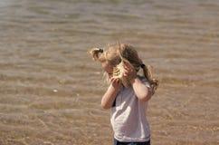 Liberdade, descoberta, aventura O menino escuta o shell na praia do mar imagem de stock