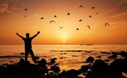 Liberdade do sentimento do homem na praia durante o nascer do sol Foto de Stock Royalty Free