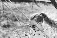 Liberdade, estilo de vida despreocupado e divertimento A menina da forma nos óculos de sol aprecia balançar no dia ensolarado Cri foto de stock