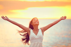 Libere a la mujer feliz que elogia la libertad en la puesta del sol de la playa