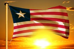 Liberia flag weaving on the beautiful orange sunset with clouds background. Liberia flag weaving on the beautiful orange sunset background royalty free stock photo