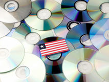 Liberian flag on top of CD and DVD pile isolated on white. Liberian flag on top of CD and DVD pile isolated Royalty Free Stock Images