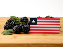 Liberian flag on a wooden panel with blackberries isolated on a. White background Royalty Free Stock Images