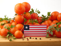 Liberian flag on a wooden panel with tomatoes isolated on a whit. E background Stock Photo