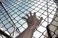 Liberté du besoin avec la main en prison Photo libre de droits