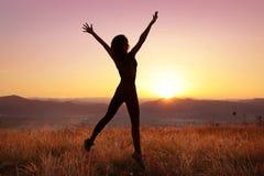 Liberté Femme sautante Free avec les bras ouverts sur le coucher du soleil Réussite T photo stock