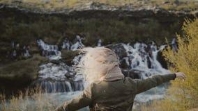 Liberté : jeune femme de déplacement regardant sur des cascades en Islande et soulevant des mains, se sentant heureux clips vidéos