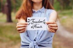 Libertad de expresión - mujer joven que lleva a cabo el papel y el texto al aire libre fotos de archivo
