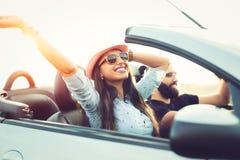 Libertad del camino abierto Pares jovenes que conducen a lo largo de la carretera nacional en coche de tragante abierto Foto de archivo libre de regalías