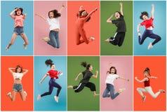 Libertad en la mudanza Mujer bastante joven que salta contra fondo anaranjado imagen de archivo