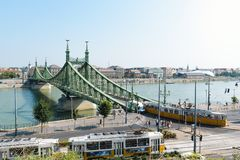 Liberty Bridge in Budapest, Hungary. The Liberty Bridge in Budapest, Hungary with some old trams in the foreground passing by stock images