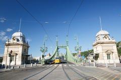 Liberty Bridge or Freedom Bridge and yellow train in Budapest Stock Photography