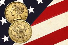 Liberty gold coin atop stars and stripes Stock Images