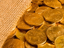 Liberty Gold Eagle one ounce coins. Gold Eagle one ounce coins being poured out of a woven sacking bag suggesting immense wealth stock images
