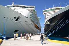 The Liberty of the Seas and The Zuiderdam. GRAND TURK, TURKS & CAICOS - JANUARY 21: People walk along a pier near the Liberty of the Seas and The Zuiderdam ships stock photo