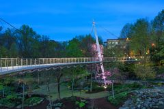 Liberty Suspension Bridge Illuminated in Greenville SC. The Liberty suspension bridge is a walkway for pedestrians over Falls Park and the Reedy River in Stock Photography