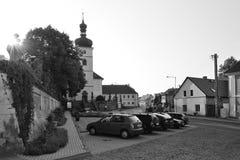 Libesice,捷克共和国- 2018年5月19日:在历史房子之间的停放的汽车与Kostel Nanebevzeti Panny桃莉的一点正方形的 免版税库存图片